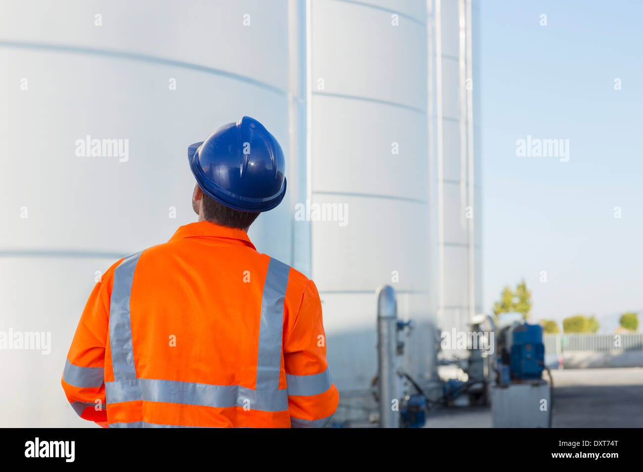 Worker looking up at silage storage towers - Stock Image