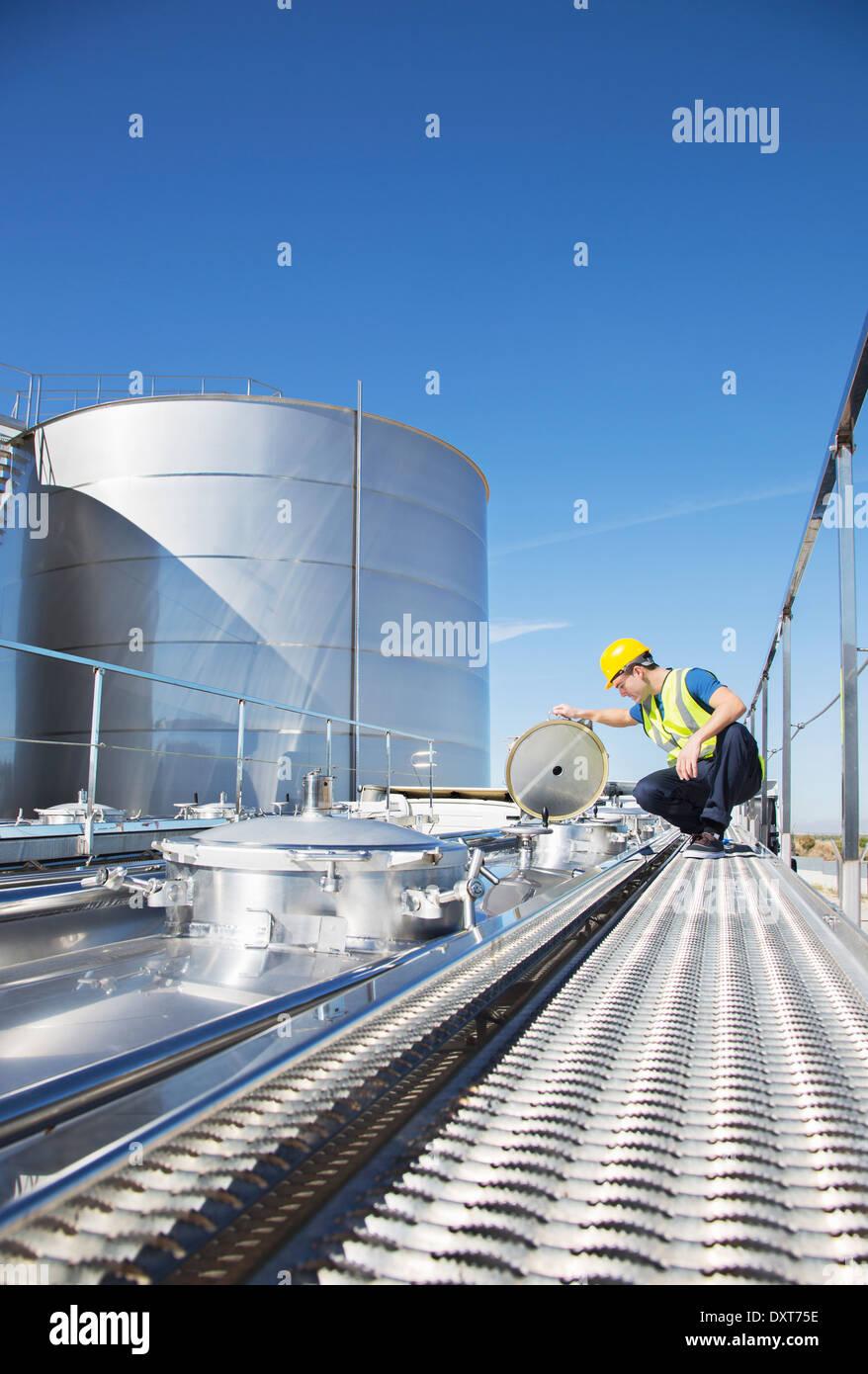 Worker on platform above stainless steel milk tanker Stock Photo