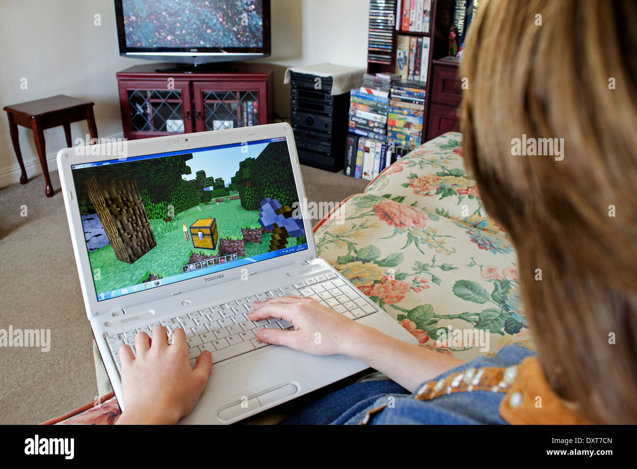 a teenage boy playing Minecraft on a laptop computer whilst watching television - Stock Image