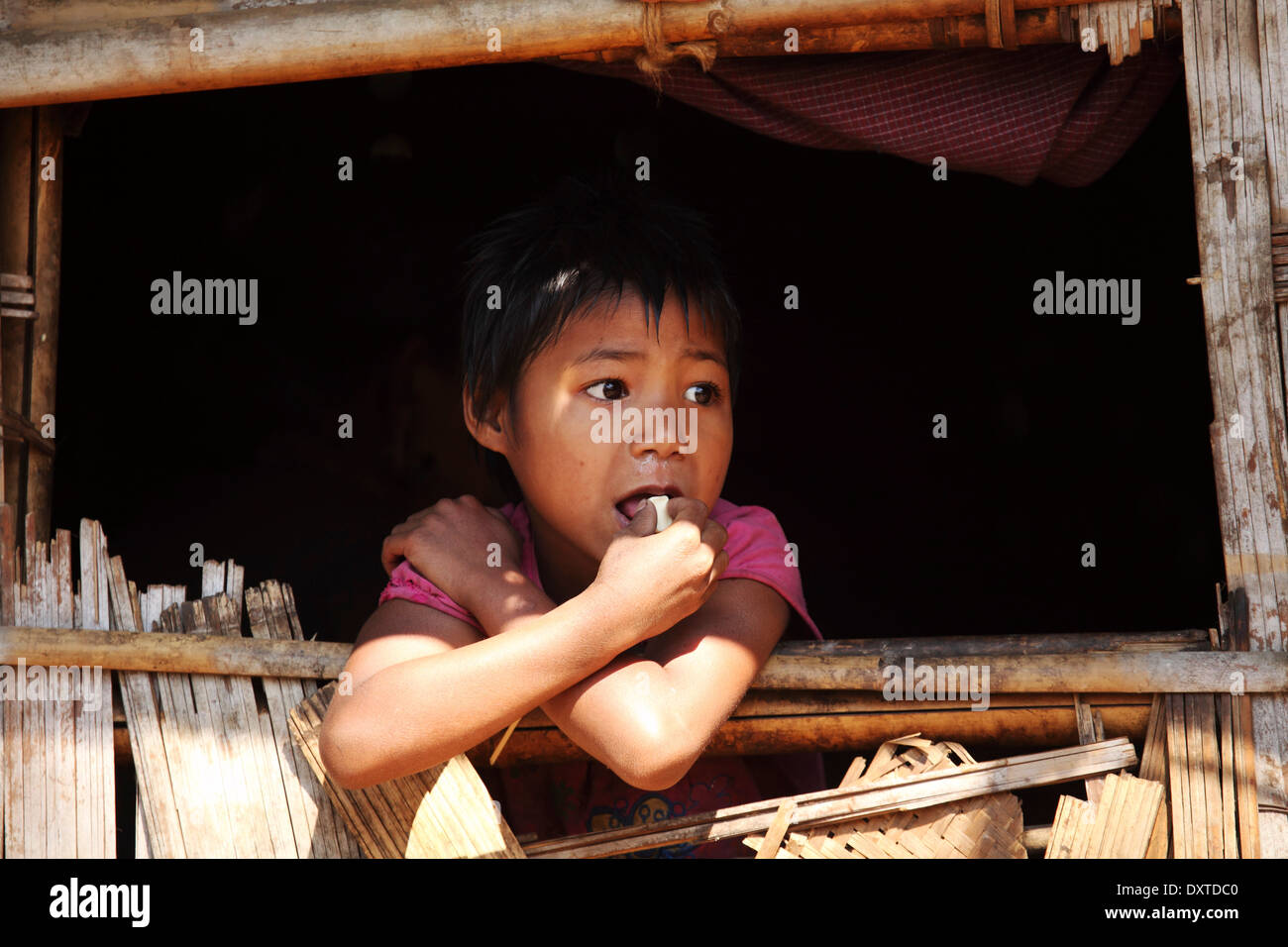 A child in a Murong tribal hut in Baganpara village in the Bandarban region of Bangladesh. - Stock Image