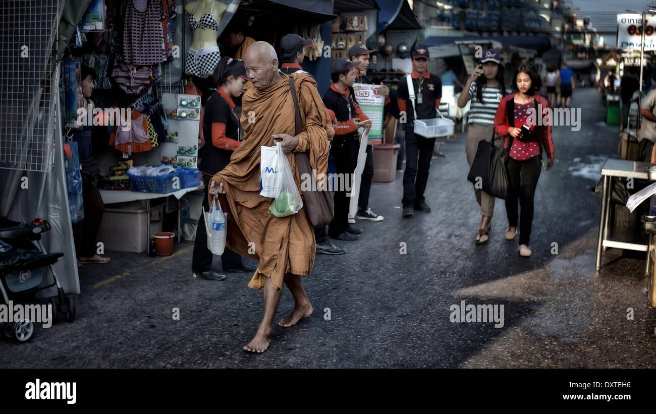 Barefoot Buddhist monk shopping at a Thai street market. Thailand S. E. Asia - Stock Image
