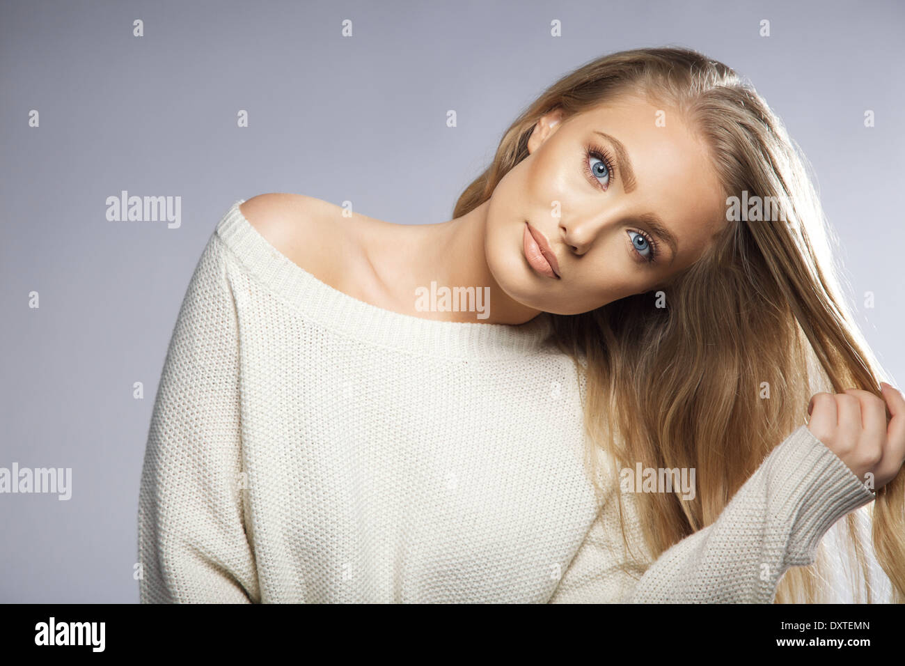 Portrait of beautiful young woman holding her hair. Young blond fashion model looking at camera while pulling her - Stock Image