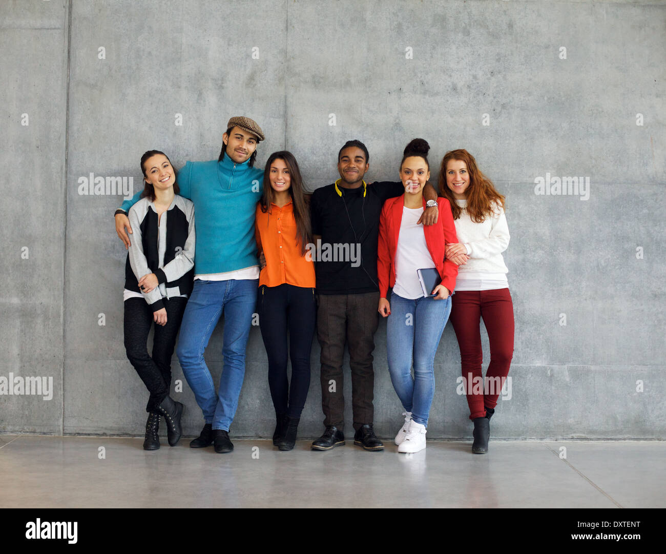 Group of stylish young university students on campus. Multiracial young people standing together against wall in college. - Stock Image
