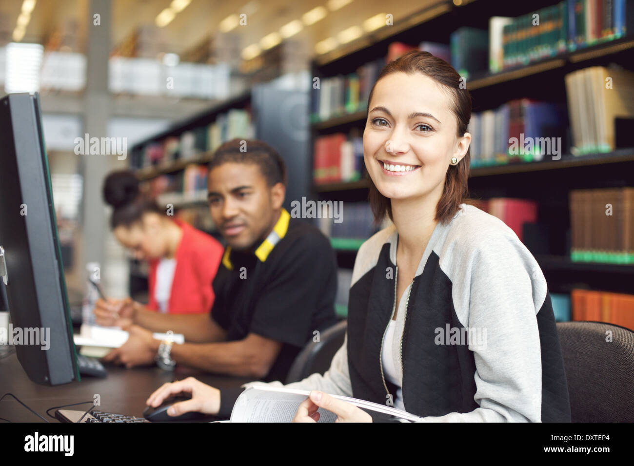 Beautiful young caucasian student sitting at table with computer looking at camera smiling. Young university students. Stock Photo