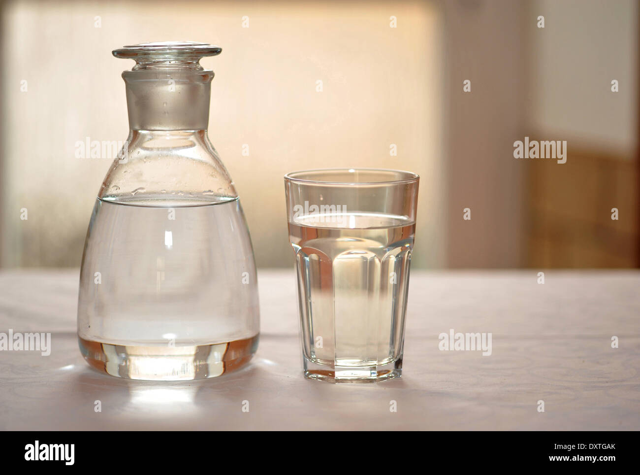 A Decorative Filled Glass Jar Next To A Filled Glass On A White