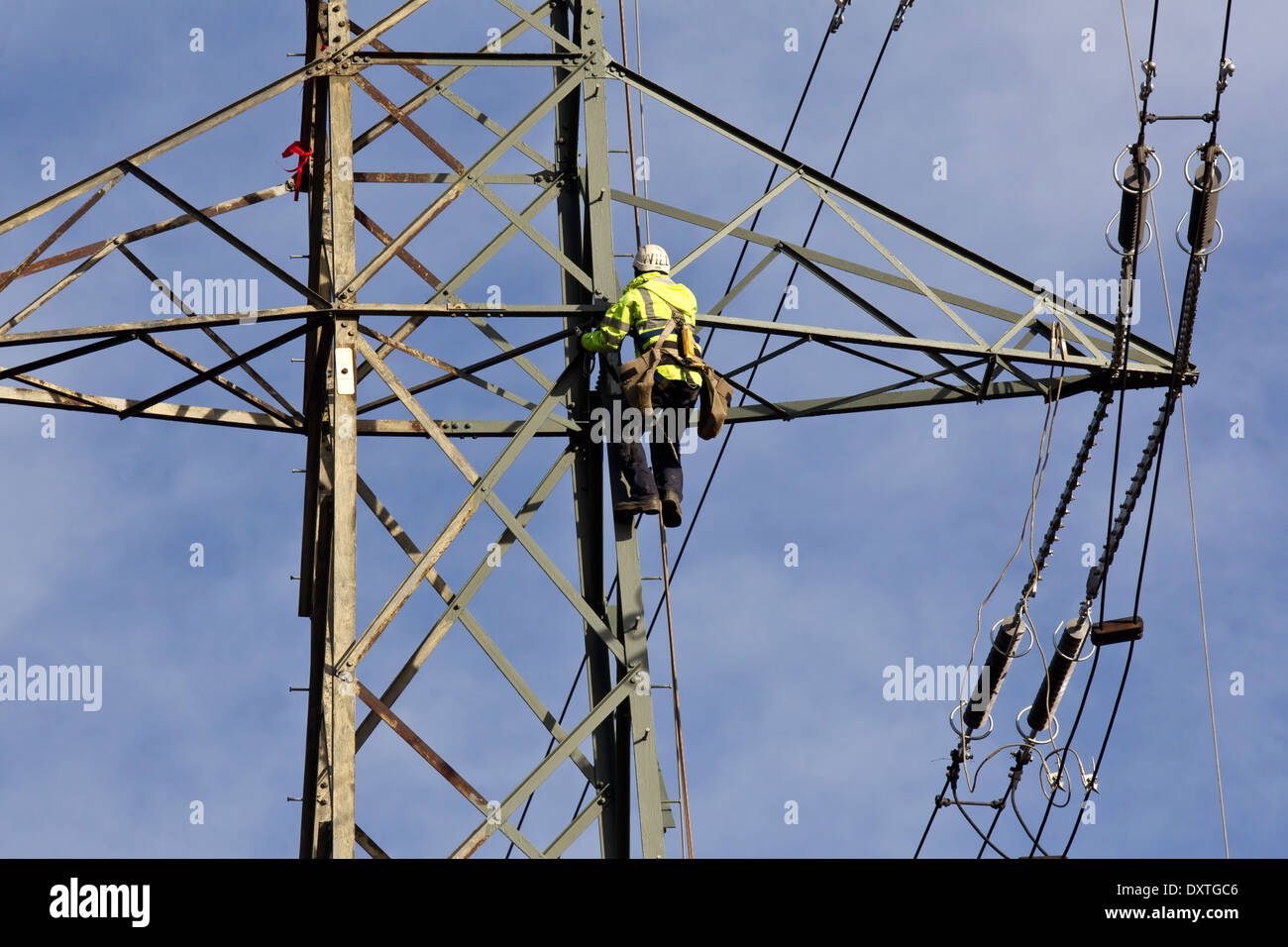 Electrical engineer climbing up an overhead electricity pylon to work on high tension power line repairs - Stock Image