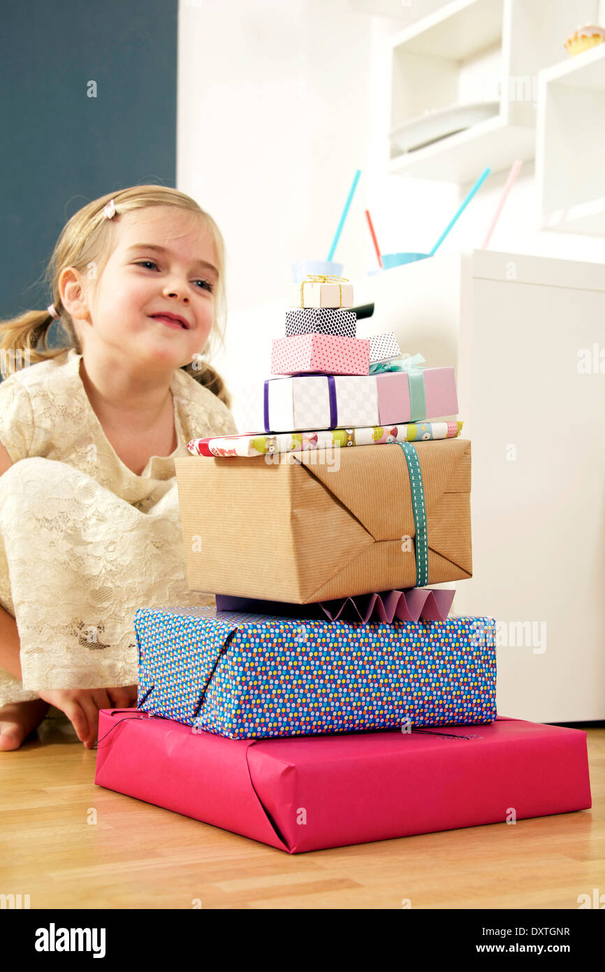 Girl on birthday looking at stack of presents, Munich, Bavaria, Germany - Stock Image
