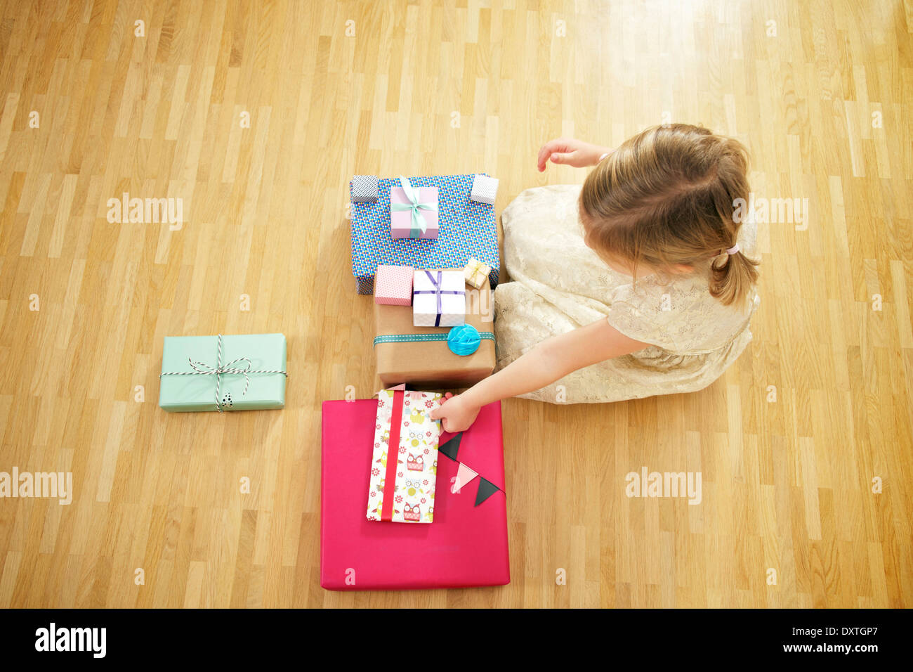 Girl on birthday party unwrapping gift boxes, Munich, Bavaria, Germany - Stock Image