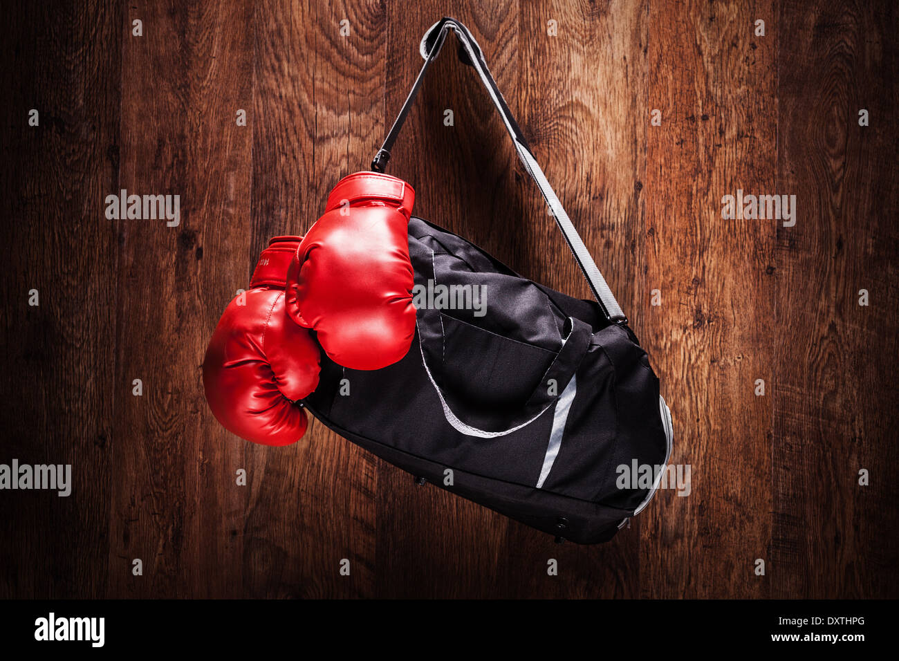 Sports bag and boxing gloves hanging on a wooden wall - Stock Image