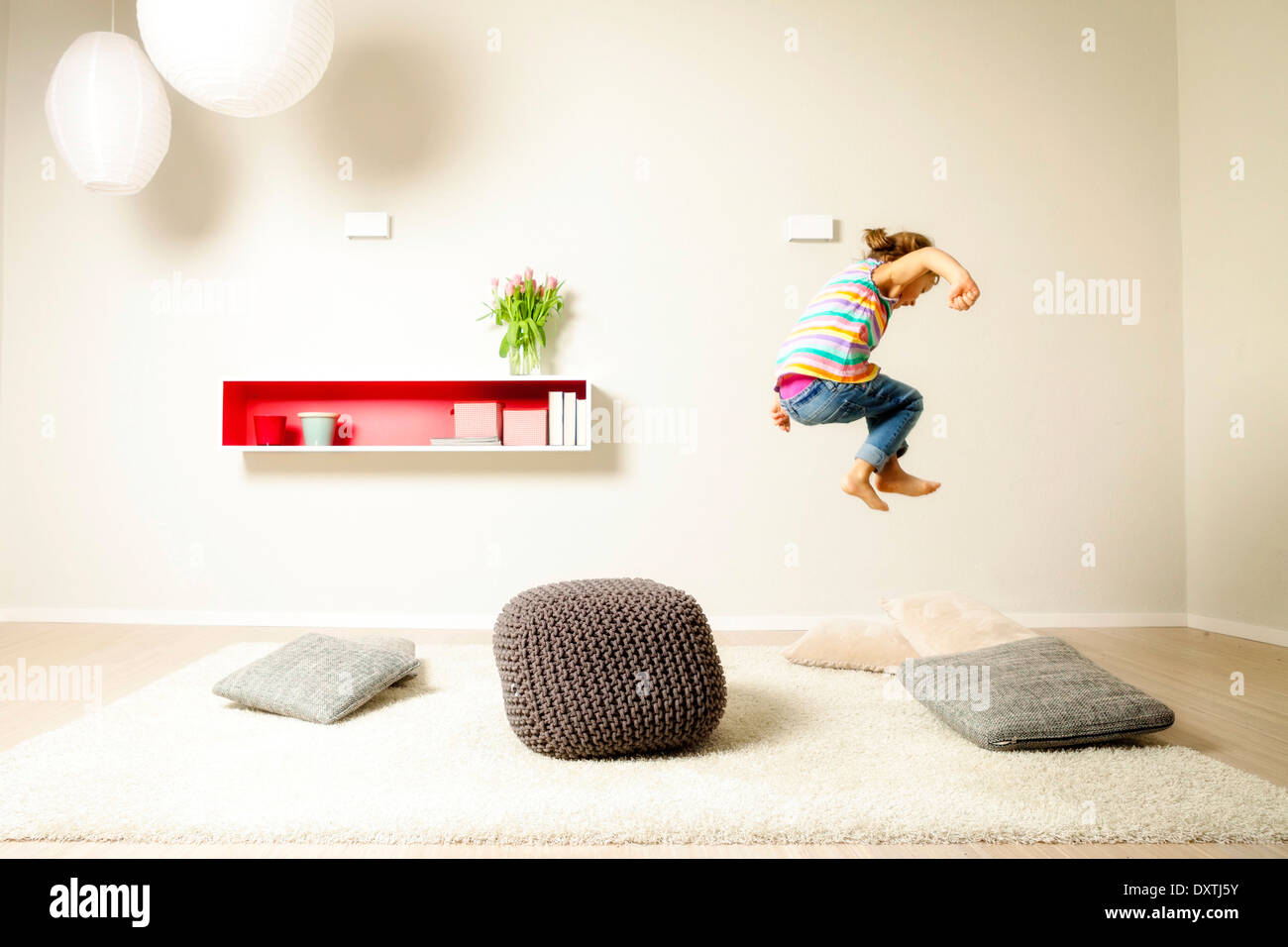 Girl jumping across cushions, having fun, Munich, Bavaria, Germany - Stock Image