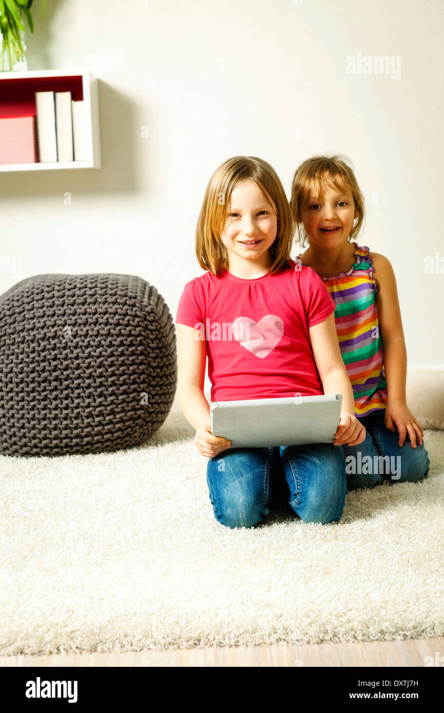 Children using tablet computer at home, Munich, Bavaria, Germany - Stock Image