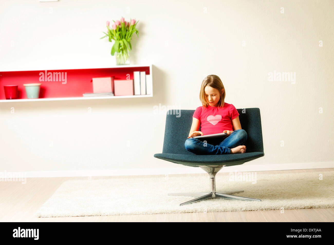 Girl sits in chair using tablet computer, Munich, Bavaria, Germany - Stock Image
