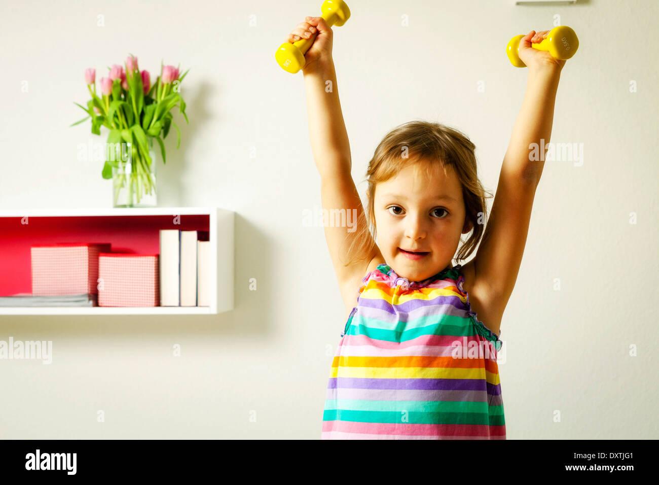 Girl exercising with dumbbells, Munich, Bavaria, Germany - Stock Image