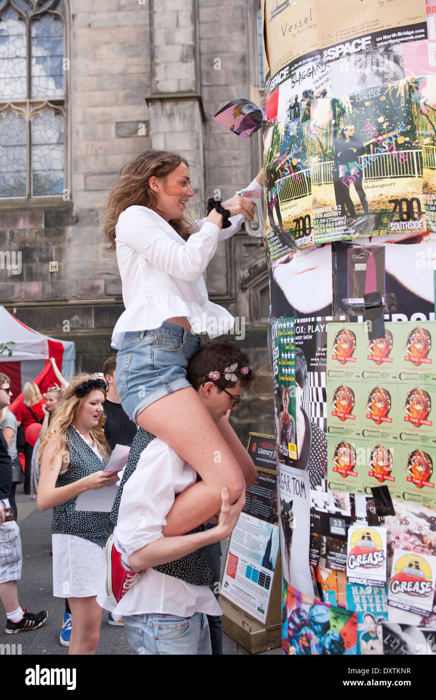 Performers adding their posters to an already crowded wall. - Stock Image