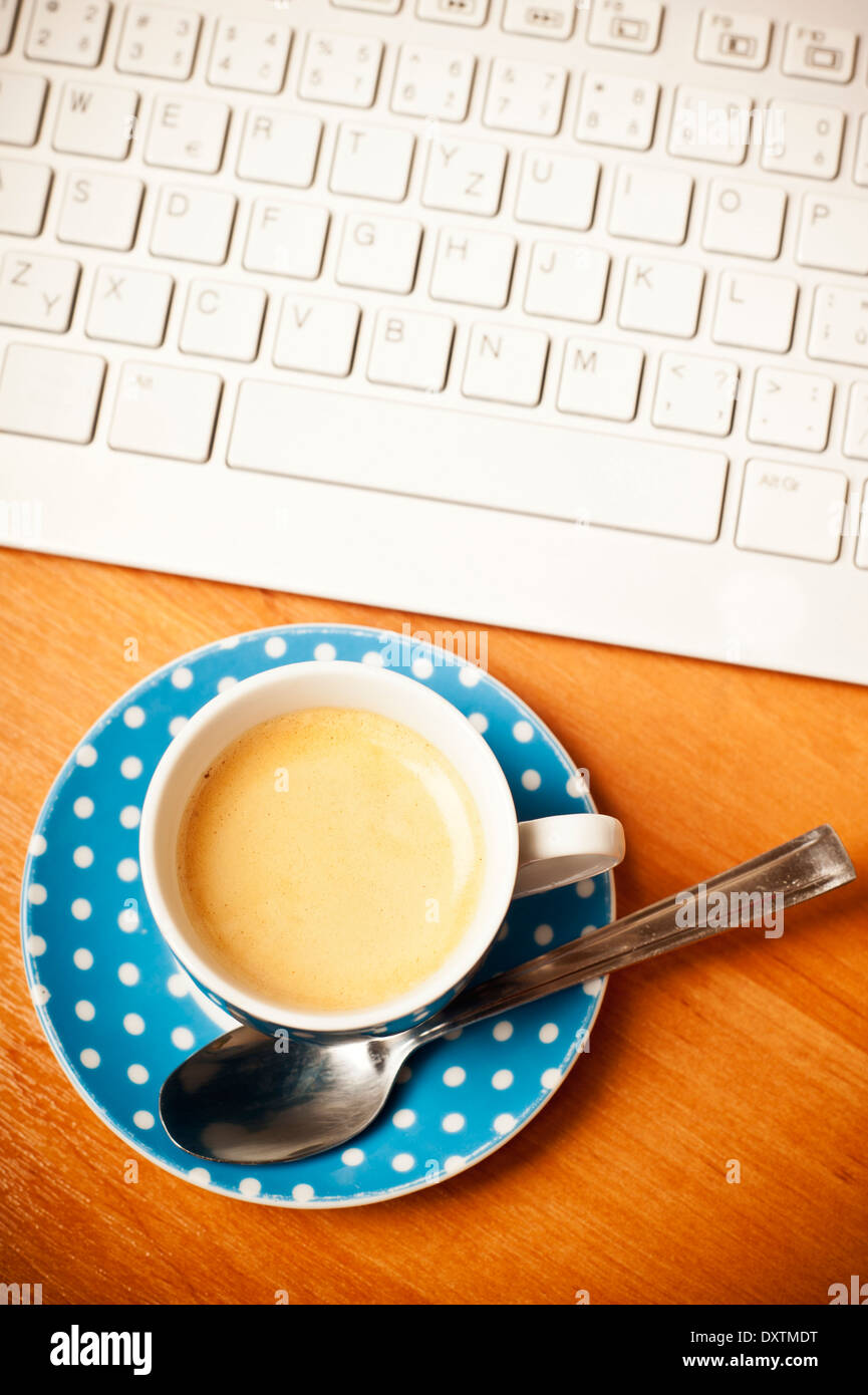 coffee cup and computer keyboard on desk, top view - Stock Image
