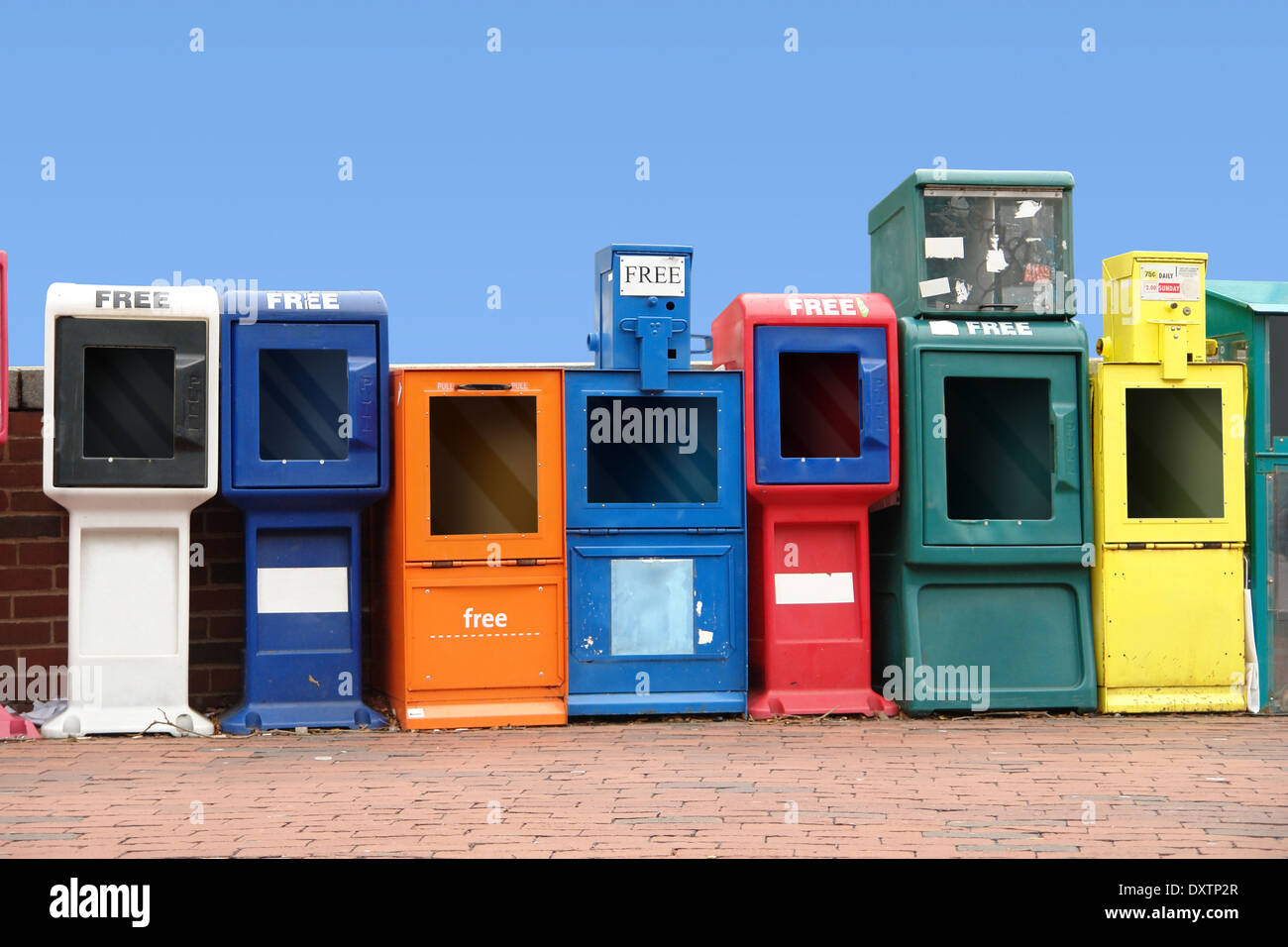 symbolic picture showing some colorful news racks standing in a row at the Harvard Square in Cambridge Massachusetts, USA) - Stock Image