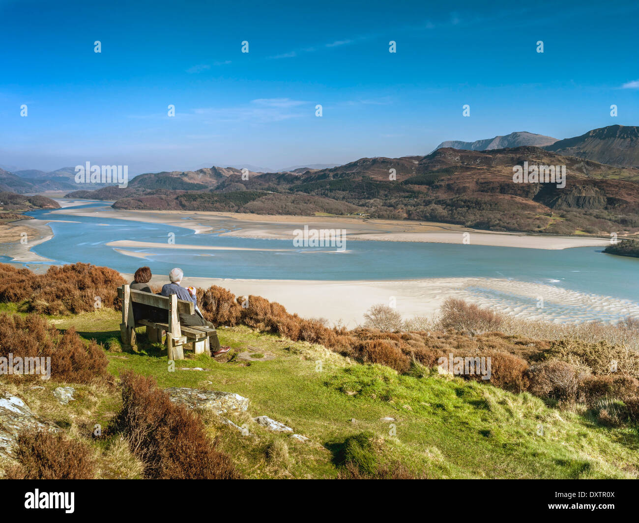 A retired couple seated on a bench at a viewpoint on Panorama Walk overlooking the Mawddach estuary and Cadair Idris range. - Stock Image