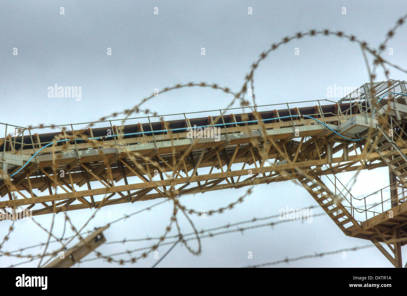 industrial conveyor belt  industrial machinery,  barbed wire - Stock Image