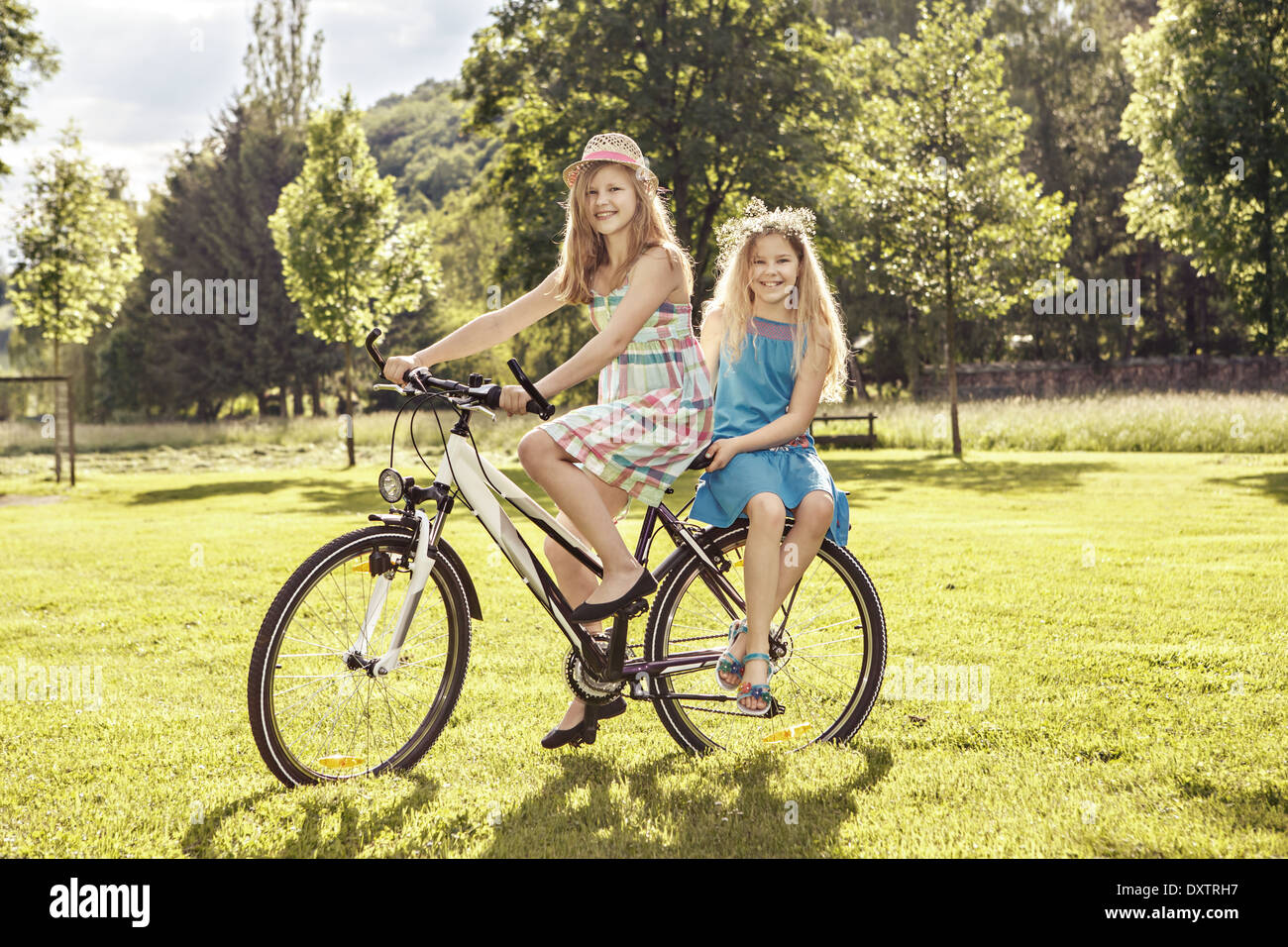 two teenage girls cycling in a summerly park - Stock Image