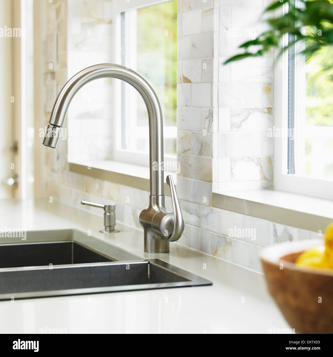 Close-up of stainless steel kitchen faucet with marble subway Stock ...