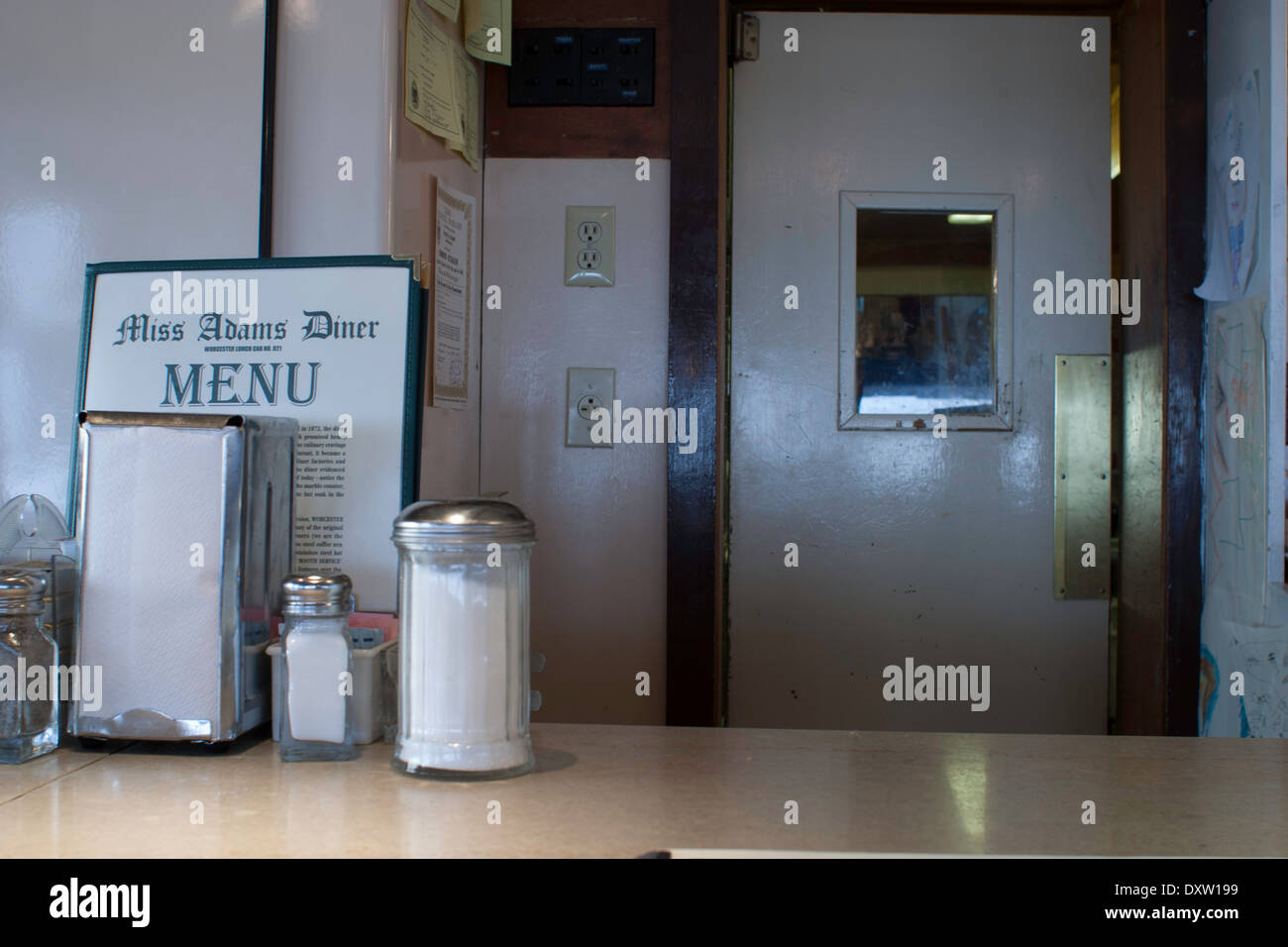Diner menu sits on the counter in a small town diner. Door to kitchen is in rear. & Diner menu sits on the counter in a small town diner. Door to ...