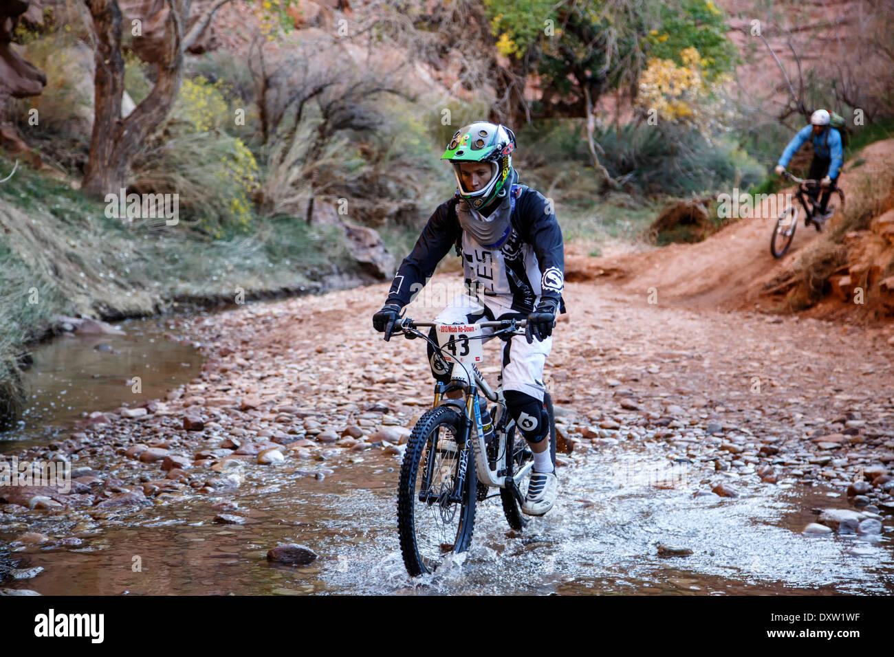 Mountain bike riders crossing Kane Springs Creek, Amasa Back Trail, near Moab, Utah USA - Stock Image