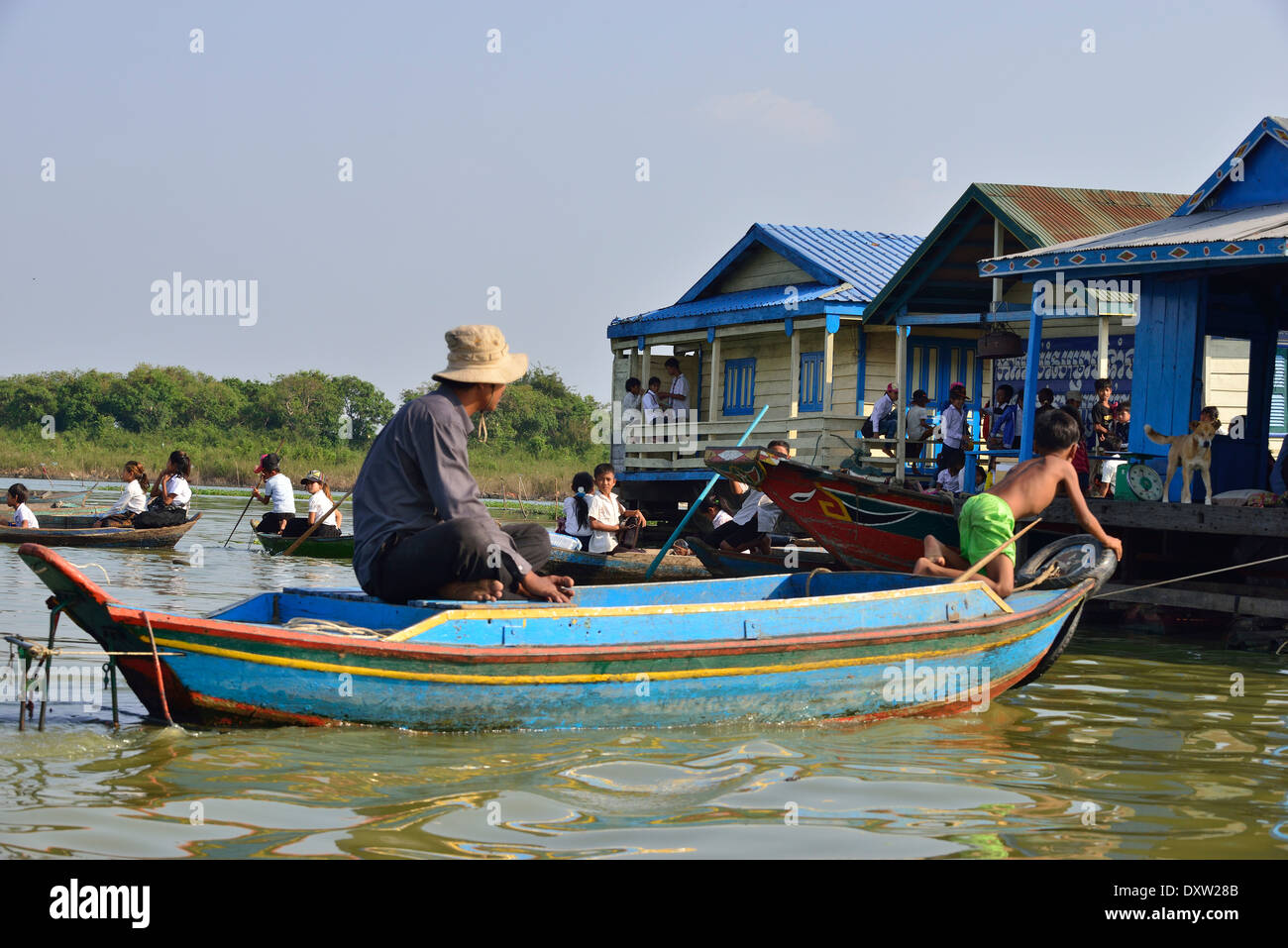 Children leaving their Floating school after classes  to paddle back to their Floating homes on the  Tonle Sap Lake, Cambodia, Southeast Asia - Stock Image