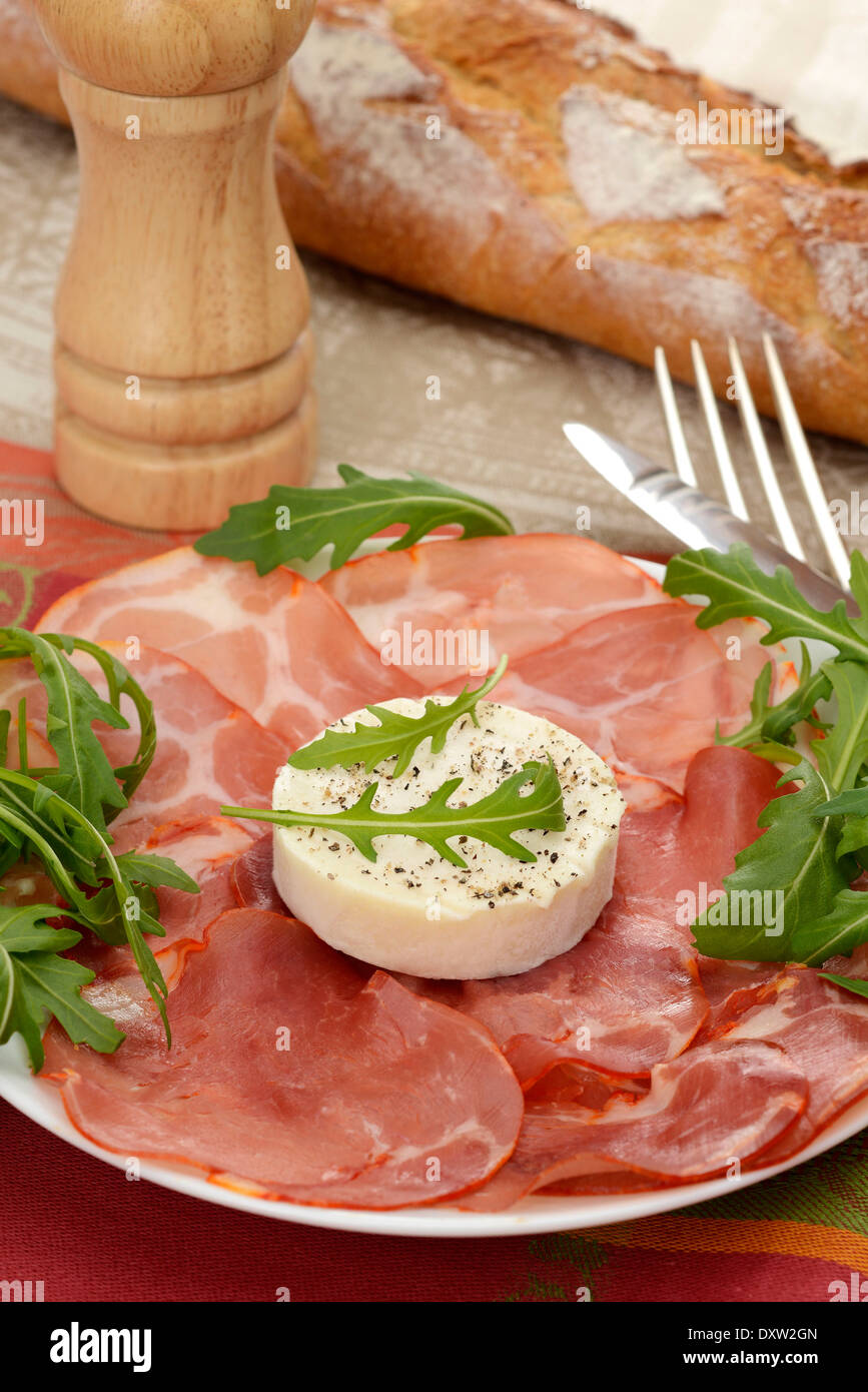 Plate of cold cuts and goat's cheese with pepper - Stock Image