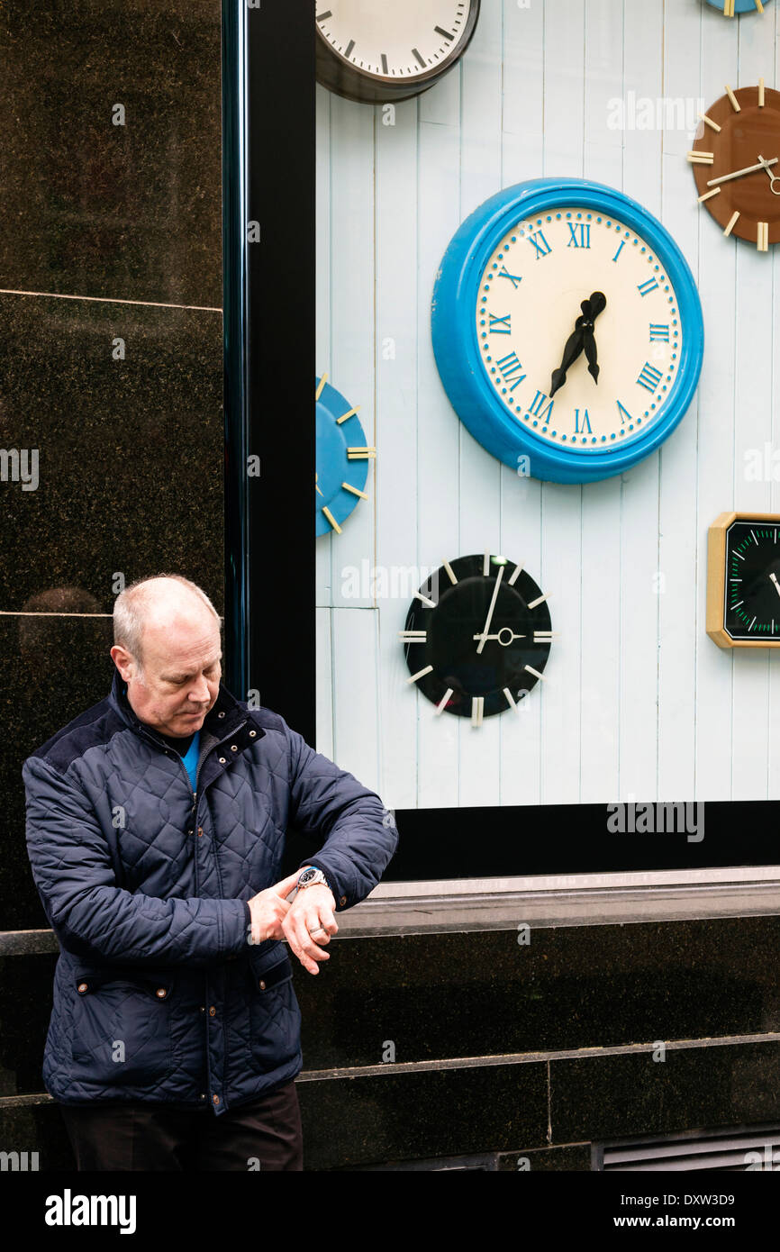 Man checking the time on his watch while standing outside a shop selling clocks. Glasgow, Scotland, UK, Great Britain - Stock Image