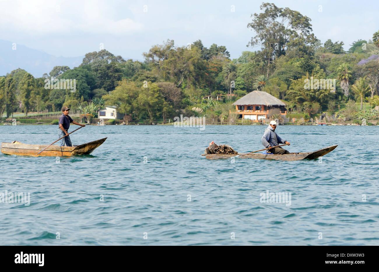 Two men paddle cayucos on Lake Atitlan. - Stock Image