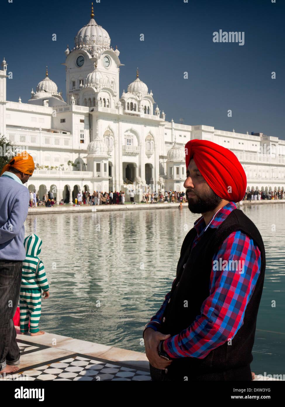 India, Punjab, Amritsar, Sri Harmandir or Darbar Sahib, Sikh man wearing red turban beside the Golden Temple Gurdwara Stock Photo
