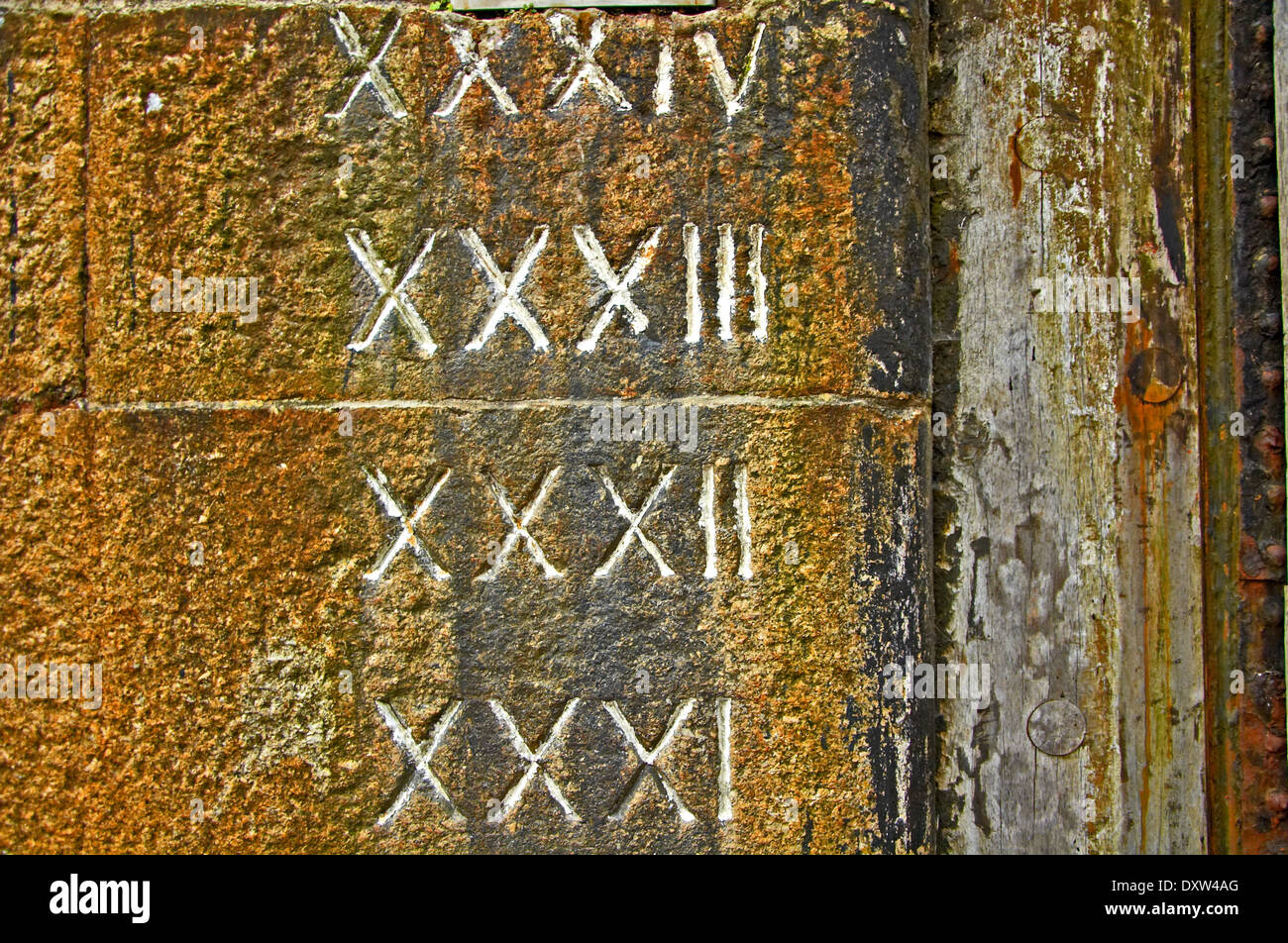 Roman numerals carved into the stonework of the old dock walls gave depth of water details. - Stock Image