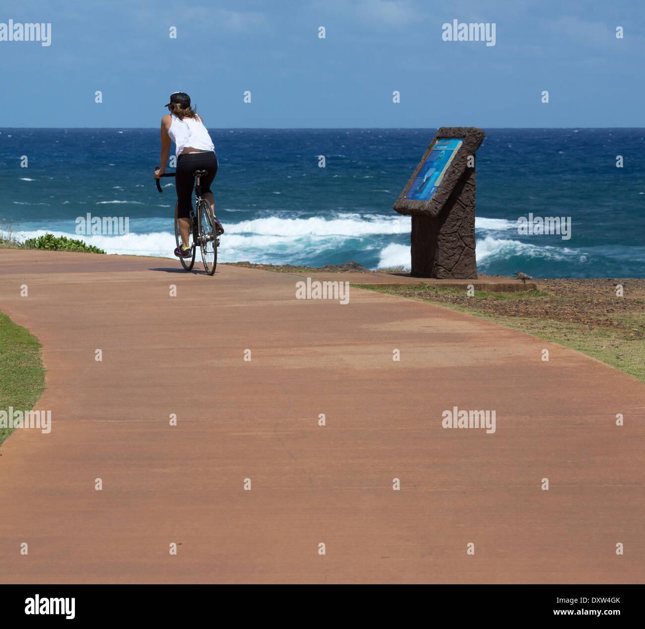 Woman riding bicycle on Kauai shared use path, Ke Ala Hele Makalae - Stock Image