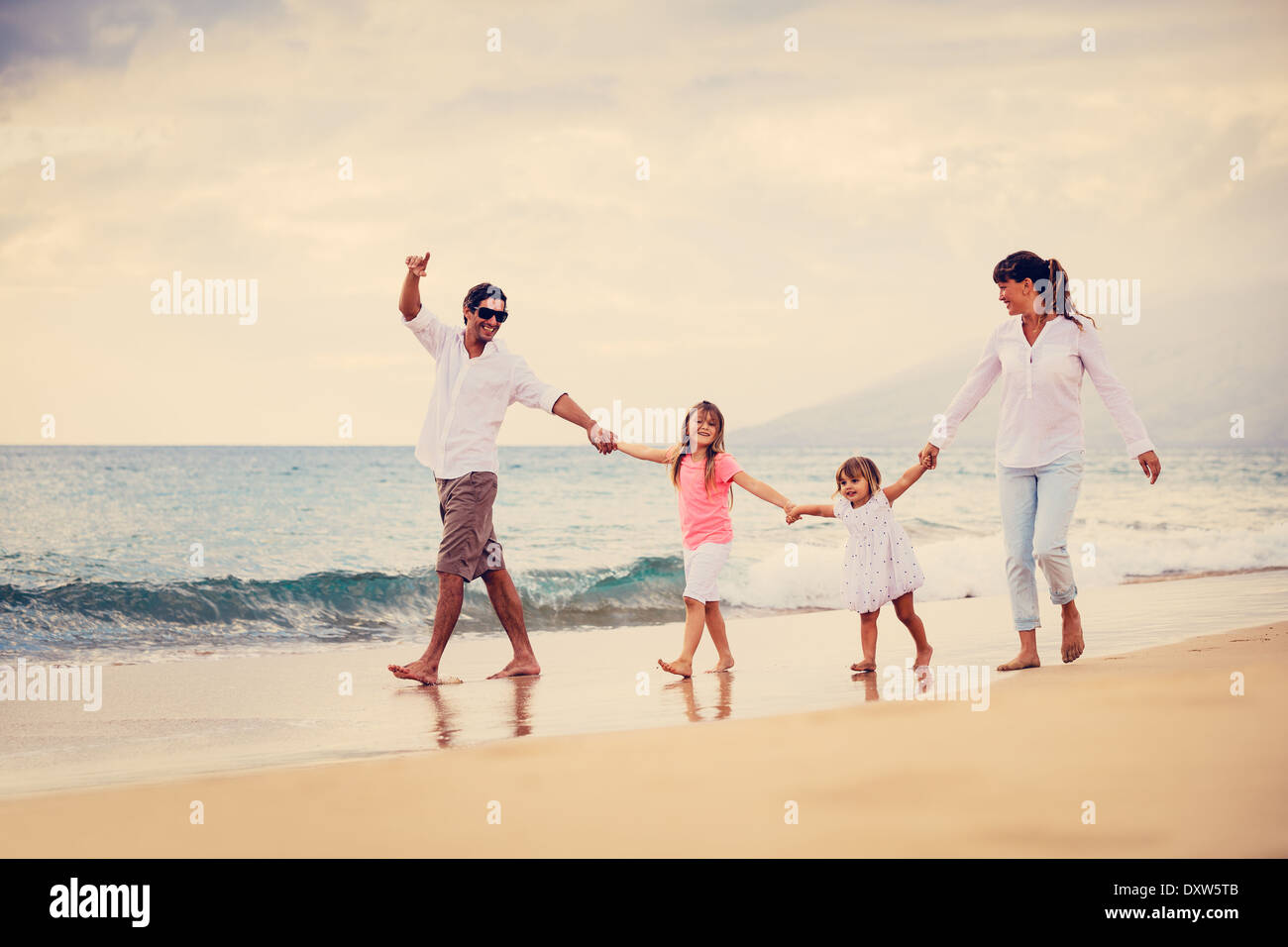 Happy Young Family have Fun Walking on Beach at Sunset - Stock Image