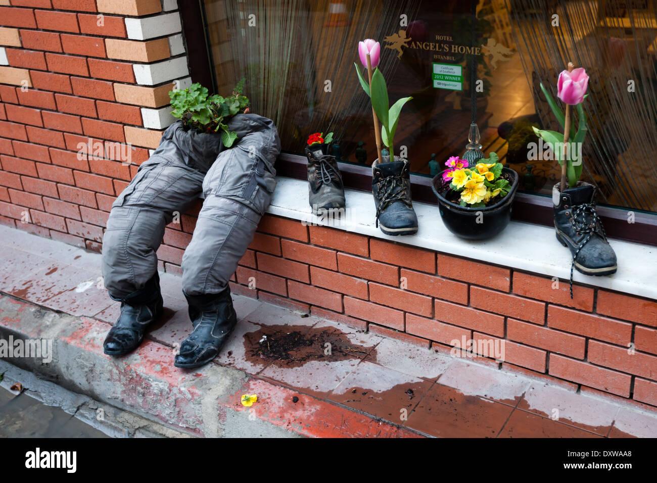 Shoes, boots, helmet ans pants serving as flowerpot - Stock Image
