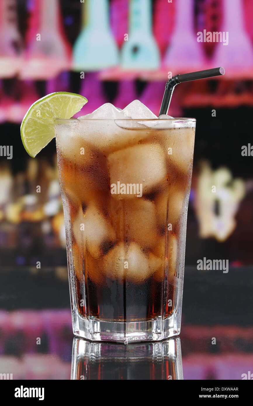 Cold cola drink in glass with ice cubes in a bar or a party - Stock Image