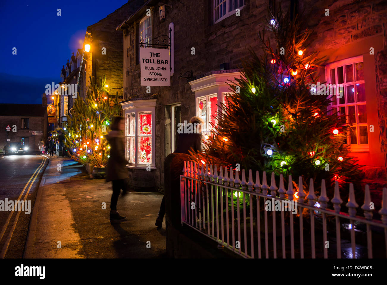 Christmas lights and trees illuminate the streets of Castleton in the Peak District Derbyshire Stock Photo