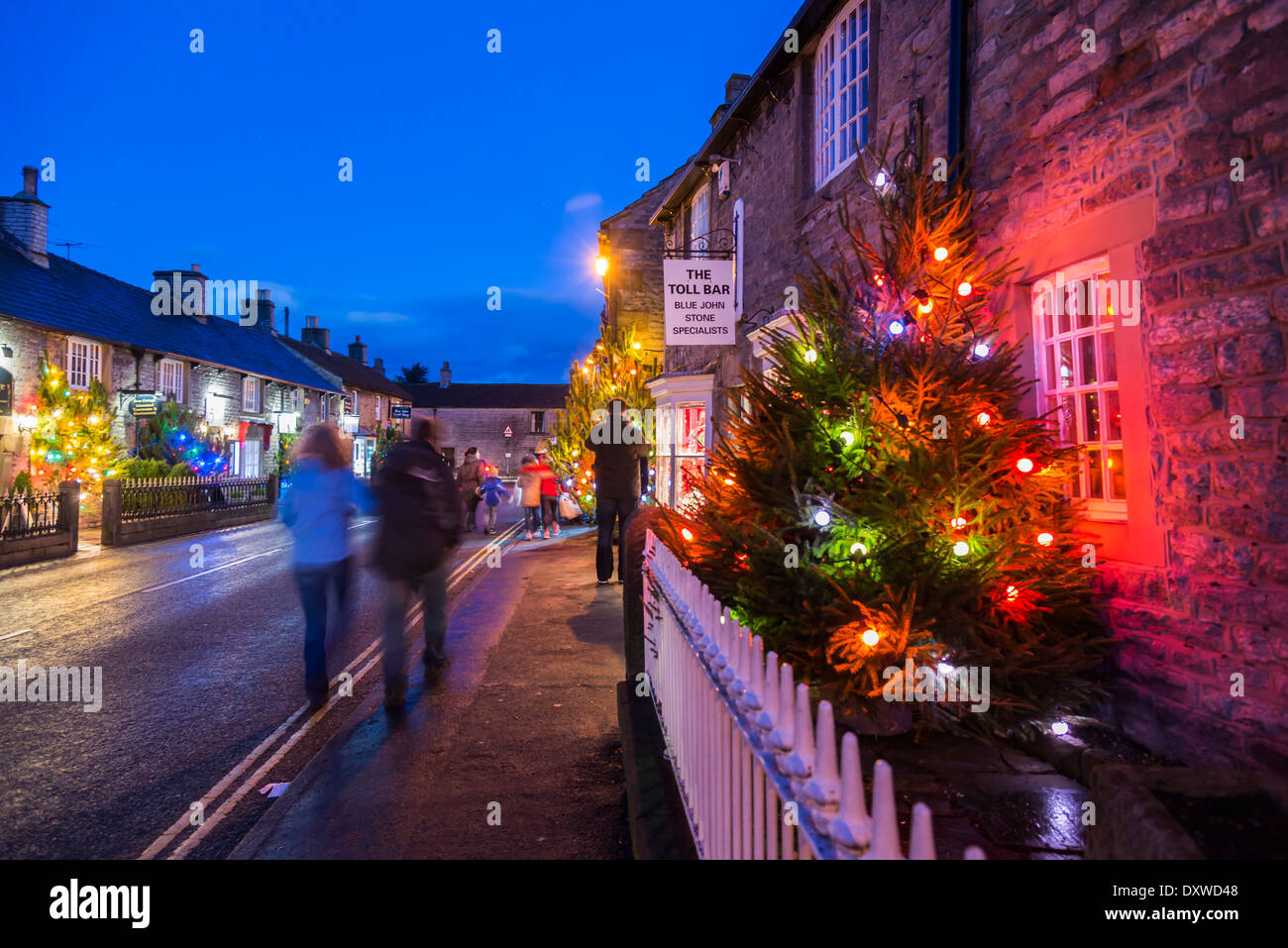Christmas lights and trees illuminate the streets of Castleton in the Peak District Derbyshire - Stock Image