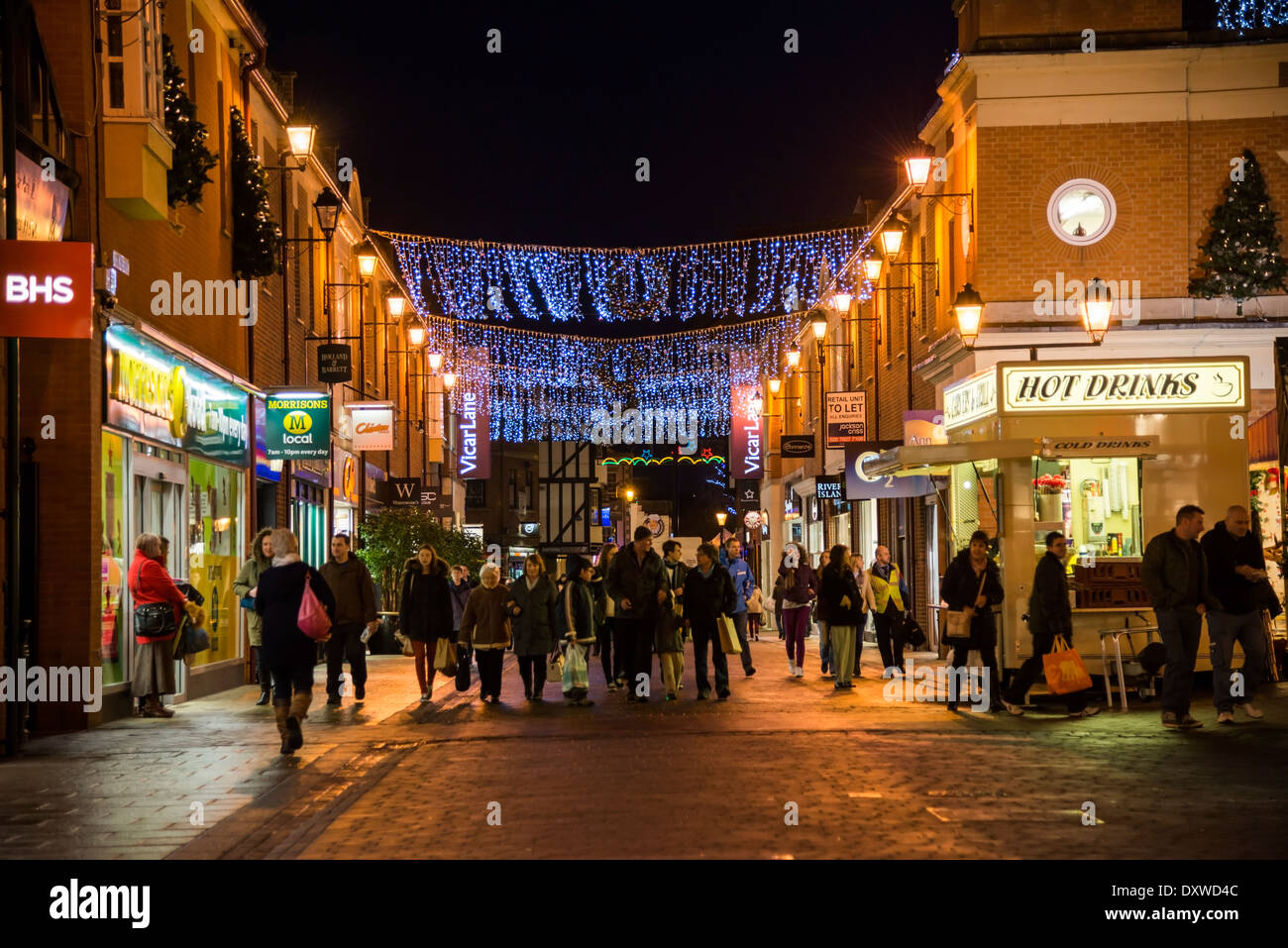 Christmas shoppers out late at night in Chesterfield town lit up with decorations and lights  Derbyshire - Stock Image