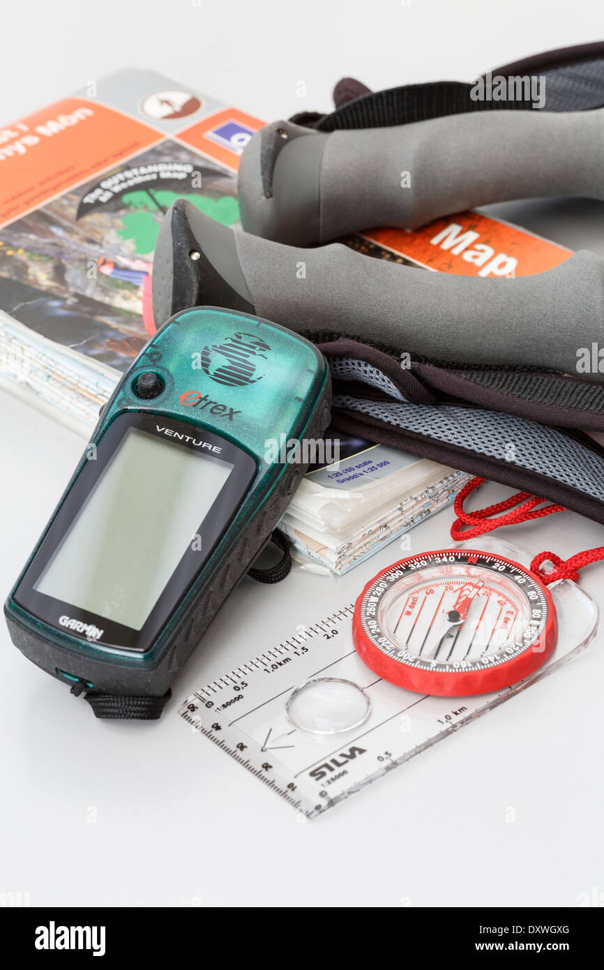 Walking equipment with plastic coated waterproof Ordnance Survey Explorer 1:25,000 map, compass, Garmin Etrex GPS and poles laid out. England UK - Stock Image