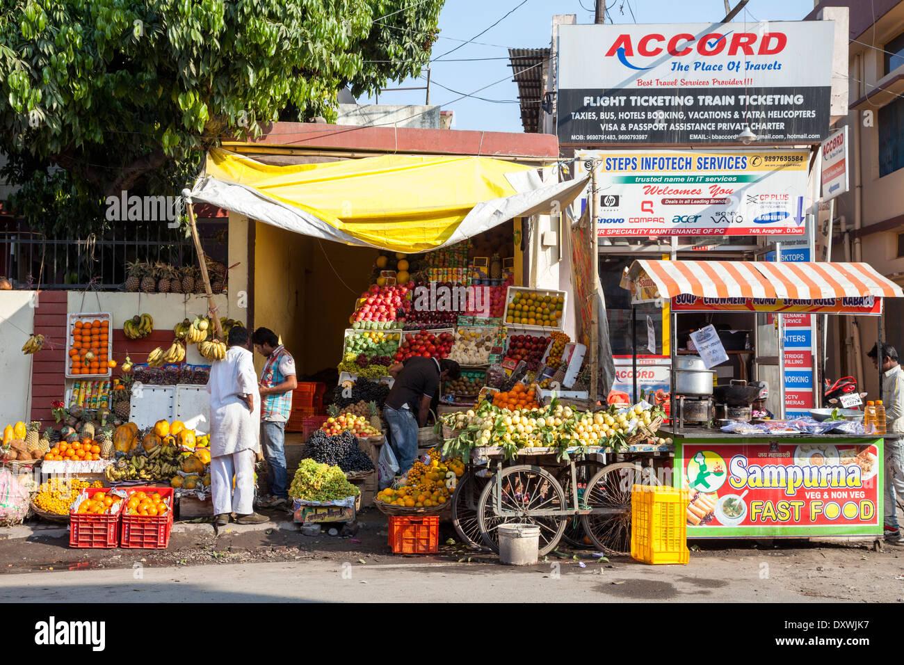 India, Dehradun. Street Scene--Fast Food, Fruit Stand, Travel Agency. - Stock Image