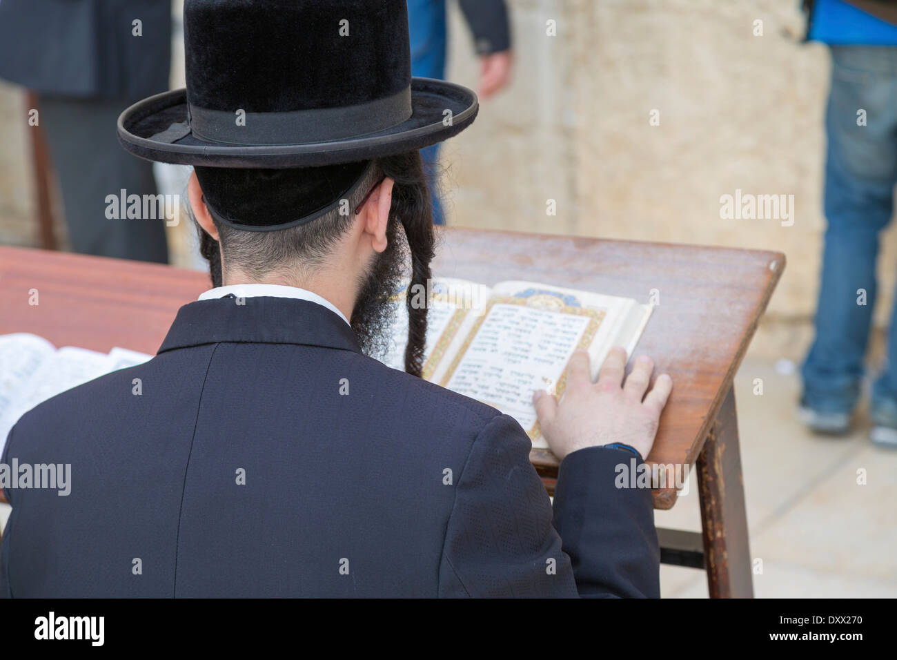 Ultra-orthodox Jew praying at the Western Wall, Wailing Wall, view over his shoulder onto the Talmud, Jerusalem, Israel - Stock Image