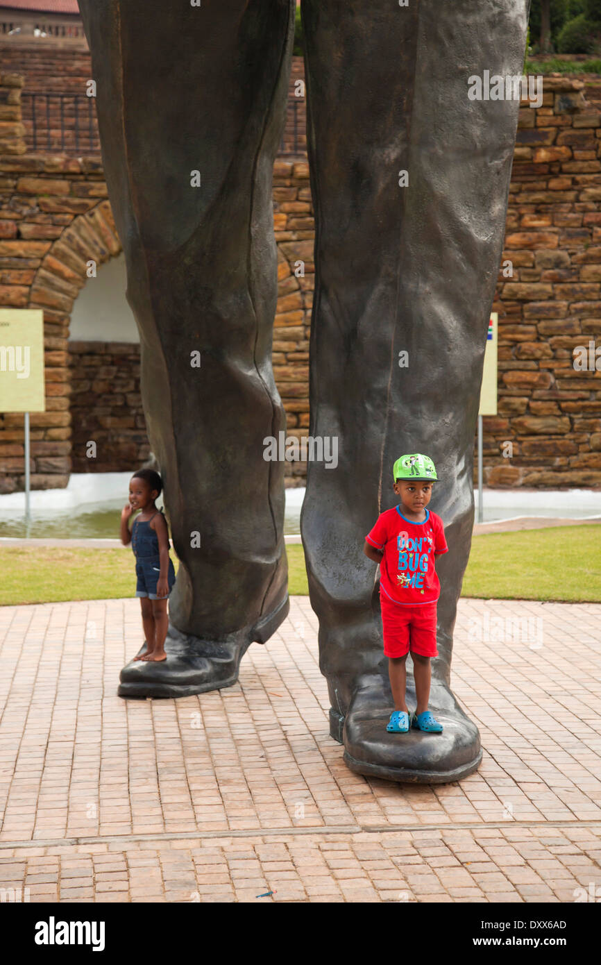 Children at the feet of the huge Nelson Mandela statue in front of the Union Buildings government buildings, Pretoria, Gauteng - Stock Image