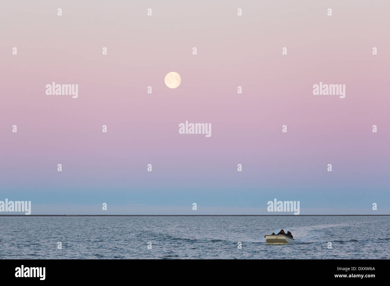 Boat returns to the shores of Barter Island under a full moon evening, Arctic Alaska - Stock Image