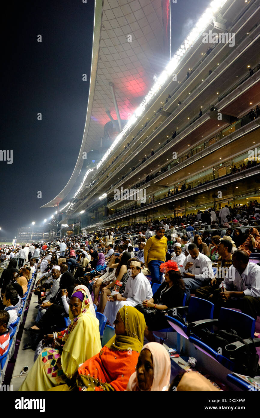Busy grandstand at Dubai World Cup horse racing championship at Meydan racecourse in Dubai United Arab Emirates - Stock Image