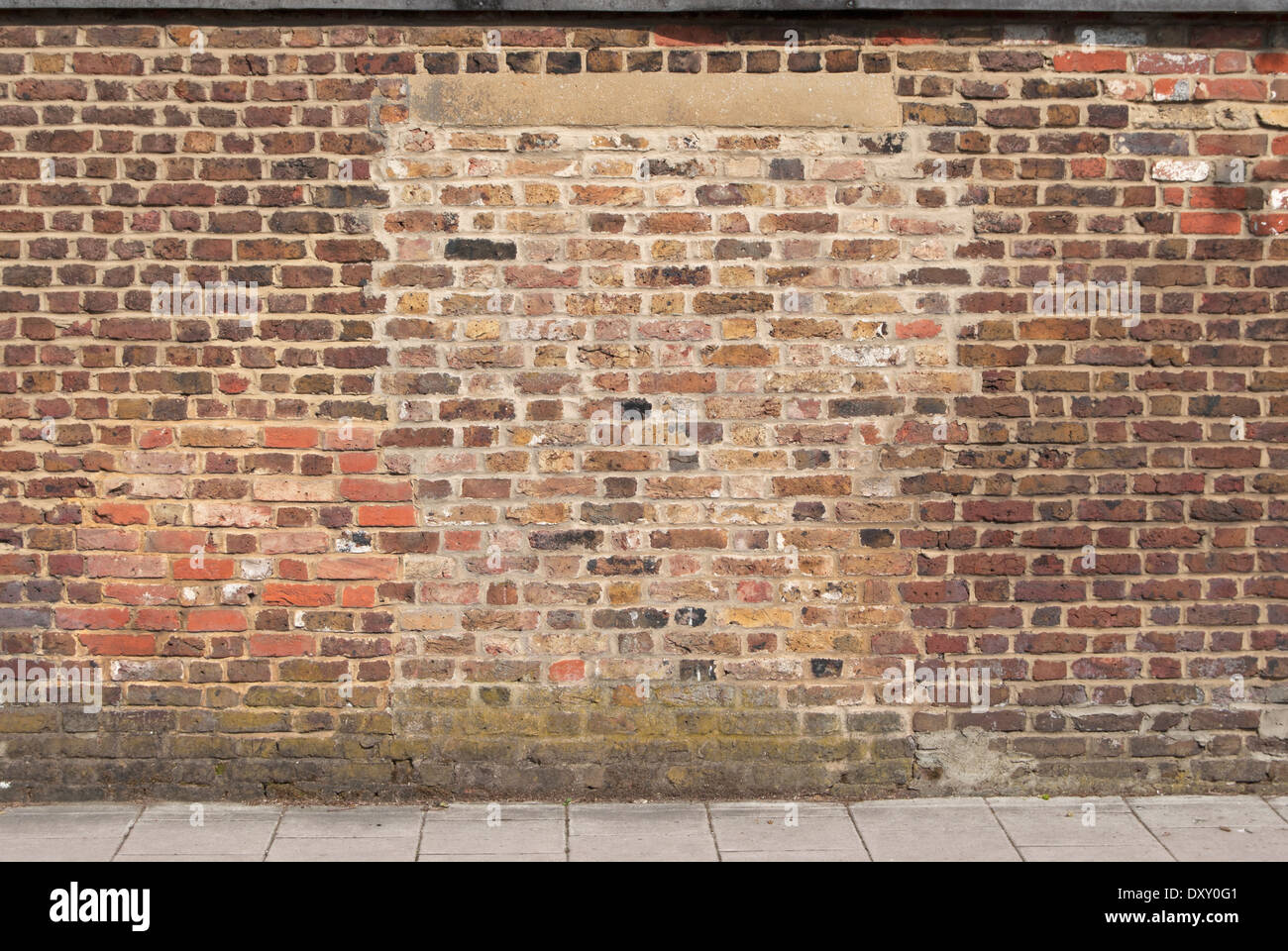brick wall showing evidence of at least two repaired sections, teddington, middlesex, england - Stock Image