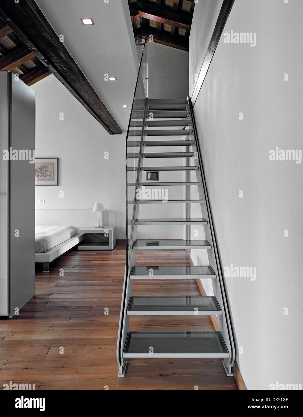 Iron Staircase And Bedroom In The Attic With Trussed Roof And Wood Floor
