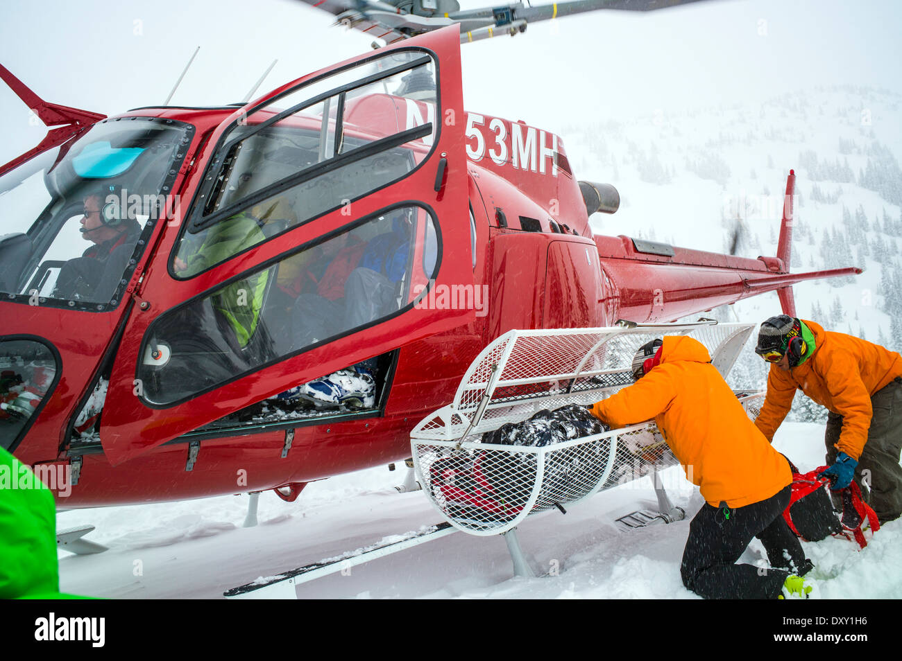 Professional mountain guides unloading skiers gear from helicopter, remote North Cascade Mountains, Washington State, USA - Stock Image