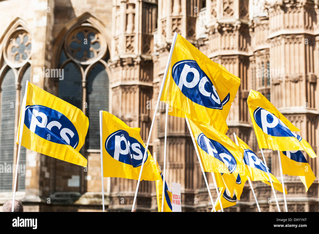 London, UK. 1st April 2014.  Flags of the trade union PCS held aloft outside the Houses of Parliament as part of the joint demonstration by probation officers and legal aid solicitors. Photographer: Gordon Scammell/Alamy Live News - Stock Image