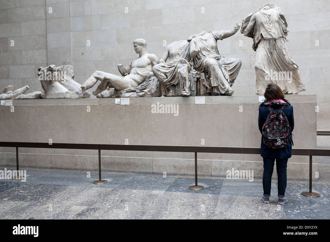 A tourist in front of the East Pediment of Parthenon in British Museum, London. - Stock Image